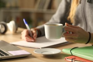 Close up of student girl hands writing on notebook holding coffee cup at night sitting on a desk at home